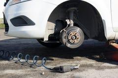 Samochód bez koła i podnosi up hydraulicznym, czekający opony zastępstwo obrazy stock