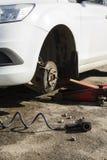 Samochód bez koła i podnosi up hydraulicznym, czekający opony zastępstwo zdjęcie royalty free