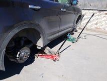 Samochód bez koła na hydraulicznym samochodowym dźwignięciu obraz stock