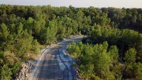 Samochód iść na drodze gruntowej między drzewami i wzgórzami 4K zbiory