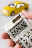 Samochód i ręka trzyma kieszeniowego kalkulatora z leasingu tekstem Zdjęcie Royalty Free