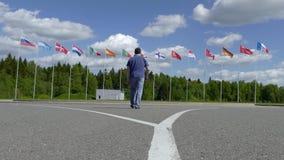 Samochód krzyżuje ścieżkę mężczyzna iść flagpoles z flagami zbiory wideo