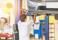 Samochód na dźwignięciu naprawiać zawieszenie w garażu z mechanikiem pracuje pod podnoszącym samochodem zmiany koła centrum zdjęcie stock