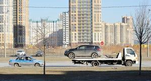 Samochód na holowniczej ciężarówce towarzyszących samochodzie policyjnym i zdjęcia stock