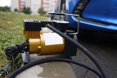 Samochód pompa Automatyczny samochodowy kompresor pomaga ciebie nie tylko ale także pompuje piłkę pompowy powietrze w kołach twój obraz stock