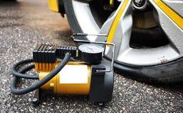 Samochód pompa Automatyczny samochodowy kompresor pomaga ciebie nie tylko ale także pompuje piłkę pompowy powietrze w kołach twój obrazy stock