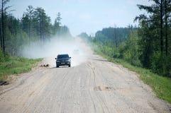Samochód przy żwiru Kolyma drogową autostradą przy Rosja Zdjęcia Stock