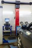 Samochód przy stojakiem dla precyzi koła alighnment czeka Obrazy Stock
