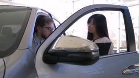 Samochód sprzedaż, azjatykciej kobiety auto handlowiec radzi atrakcyjnego konsumpcyjnego faceta w kabinowej maszynie podczas gdy  zbiory