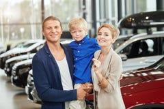 Samochód sprzedaży centre młoda rodzina z dziecko chłopiec w samochodowym bublu obrazy stock