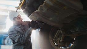 Samochód usługa - mechanik sprawdza koło SUV, szeroki kąt, backlight Obraz Royalty Free