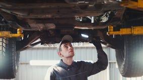 Samochód usługa - mechanik sprawdza zawieszenie SUV fotografia stock