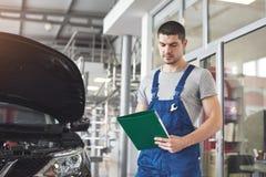 Samochód usługa, naprawa, utrzymanie i ludzie pojęć, - auto mechanika kowal z schowkiem przy warsztatem lub mężczyzna obraz royalty free