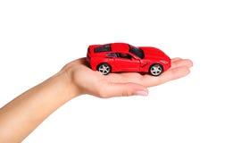 Samochód w żeńskiej ręce odizolowywającej na bielu Zdjęcia Stock