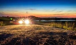 Samochód z jaskrawym światłem w pięknym góra krajobrazu zmierzchu słońcu Obraz Royalty Free