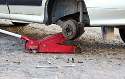 Samochód załatwiający w garażu, Hydrauliczny podłogowy dźwigarki dźwignięcie samochód, koło bez opony, klucza przecinający drogow obraz stock