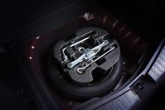 Samochodowa dźwigarka i koło zmienia narzędziowego zestaw w dodatkowej oponie zdjęcia stock