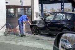 Samochodowa domycie stacja Mężczyzna pracownik myje samochodowych koła z wysokość naciska wodą zdjęcie royalty free