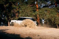 Samochodowa Land Rover Range Rover przejażdżka przy piasek drogą blisko sosnowego lasu przy dniem Zdjęcie Stock