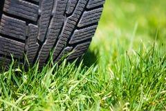 Samochodowa opona na zielonej trawie Obrazy Stock