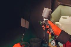 Samochodowa remontowa us?uga Pracownika malarz sprawdza koloru dopasowywanie przed malowa? rozpyla? czarnego ciecz na trafnym tal obrazy stock