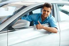 Samochodowa sala wystawowa Szczęśliwy klient wśrodku samochodu Jego sen obrazy stock