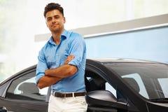 Samochodowa sala wystawowa Szczęśliwy mężczyzna blisko samochodu Jego sen Zdjęcie Stock