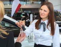 Samochodowa sprzedawczyni wręcza nad kluczami dla nowego samochodu młoda kobieta Obrazy Stock