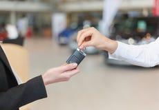Samochodowa sprzedawczyni wręcza nad kluczami dla nowego samochodu młoda kobieta Fotografia Royalty Free