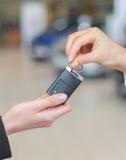 Samochodowa sprzedawczyni wręcza nad kluczami dla nowego samochodu młoda kobieta Zdjęcie Stock