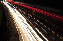 Samochodowe lekkie linie na higway podczas ruchu drogowego dżemu przy nocą Zdjęcia Royalty Free