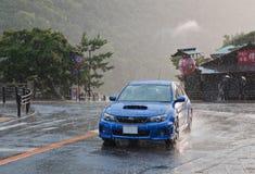 Samochodowe przejażdżki poścą na miasto drodze przy opady deszczu. Obrazy Stock
