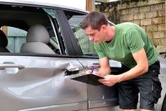 Samochodowego ciała mechanik sprawdza out szkodę Zdjęcie Stock