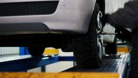 Samochodowego mechanika śrubowania szpilki samochodowy koło samochód w garażu, suwak zdjęcie wideo