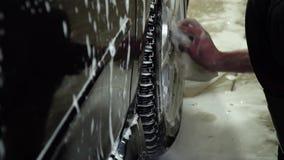 Samochodowego obmycia A samochodowego obmycia pracownik myje samochód Mężczyzna myje samochód z gąbką z pianą Zakończenie zbiory
