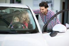 Samochodowego sprzedawcy handshaking z rozochoconą nabywcą Obrazy Royalty Free
