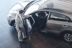 Samochodowego sprzedawcy otwarcia drzwi klient zdjęcia stock