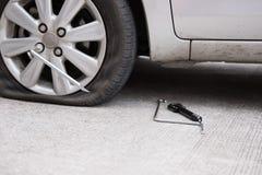 Samochodowej opony przeciek przez gwoździa ubijanie płaska opona na drodze flatt fotografia royalty free