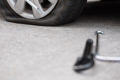 Samochodowej opony przeciek przez gwoździa ubijanie płaska opona na drodze flatt zdjęcia royalty free