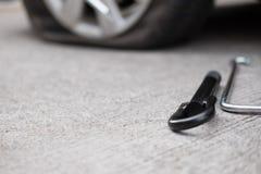 Samochodowej opony przeciek przez gwoździa ubijanie płaska opona na drodze flatt obrazy royalty free