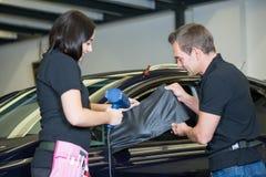 Samochodowi opakunkowi specjaliści zawija strony lustro z węgiel folią Fotografia Royalty Free