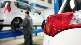 Samochodowi szczegóły mechanik pracuje blisko podnoszącego samochodu - auto reflektoru zakończenie up w diagnostyk usługa - zdjęcie wideo