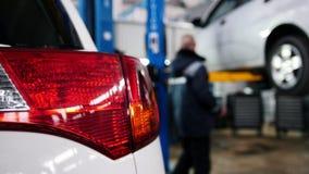 Samochodowi szczegóły mechanik pracuje blisko podnoszącego samochodu - czerwony auto reflektoru zakończenie up w diagnostyk usług zbiory wideo