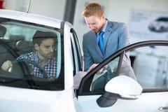 Samochodowy agent i klient w samochodowej sala wystawowej Zdjęcia Stock