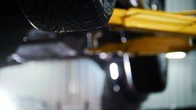Samochodowy diagnostyk - mechanika odśrubowania przyrząd podczas gdy pracujący pod podnoszącym samochodem, skupiający się tło zbiory wideo