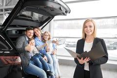 Samochodowy handlowiec pozuje przy kamerą z rodziną, nabywcy nowy samochód zdjęcia stock