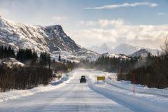 Samochodowy jeżdżenie na śnieżnej drodze z pasmem górskim obrazy stock