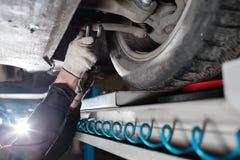 Samochodowy mechanik egzamininuje samochodowego zawieszenie podnoszący samochód przy remontową stacją obsługi obraz stock