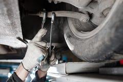 Samochodowy mechanik egzamininuje samochodowego zawieszenie podnoszący samochód przy remontową stacją obsługi zdjęcie royalty free