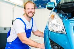 Samochodowy mechanik i samochód w usługowym warsztacie zdjęcia royalty free